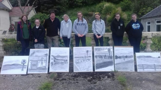 DofE participants standing in front of their artwork. Sketches of landscapes.