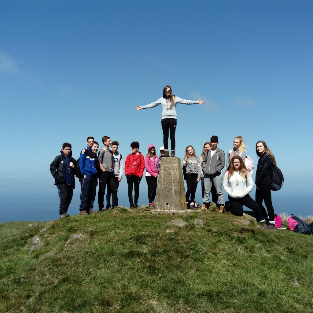 DofE participants at the top of a mountain with one standing on the cairn