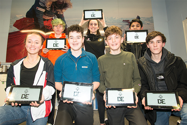 several young people holding tablets