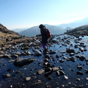 DofE participant walking on rocks over a stream