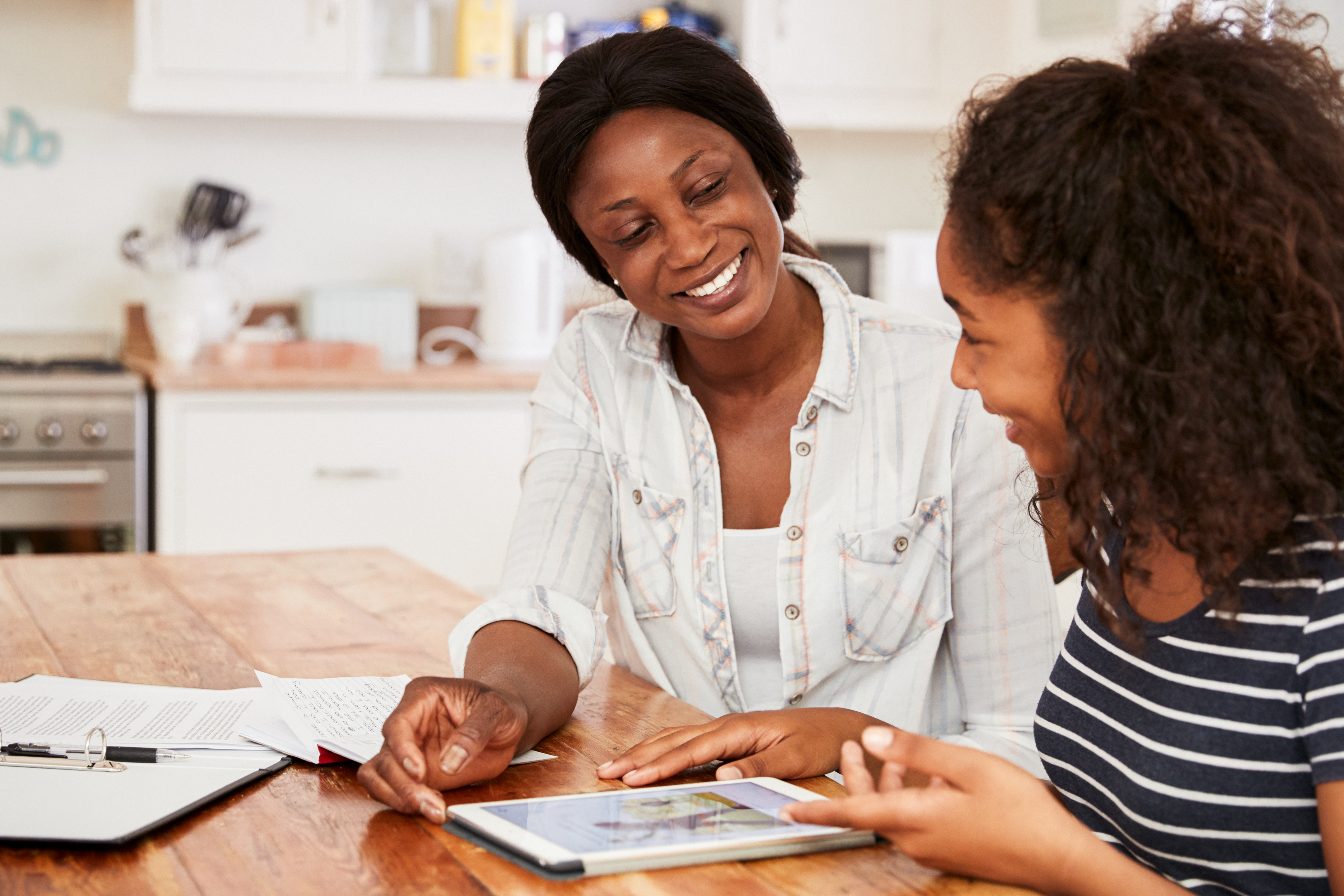 Parent and child smiling and working on a tablet