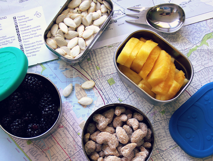 Metal tins of nuts and fruit resting on map.