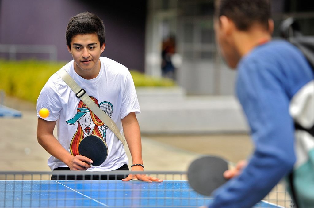 Two young men playing ping pong