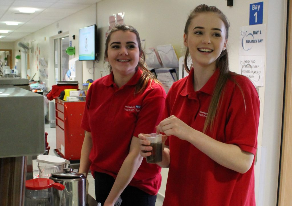 Two young DofE volunteers in NHS hospital wearing red tshirts