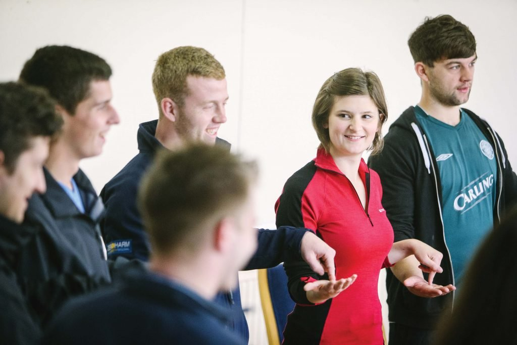 Four young men and one young women taking part in team building exercise and smiling