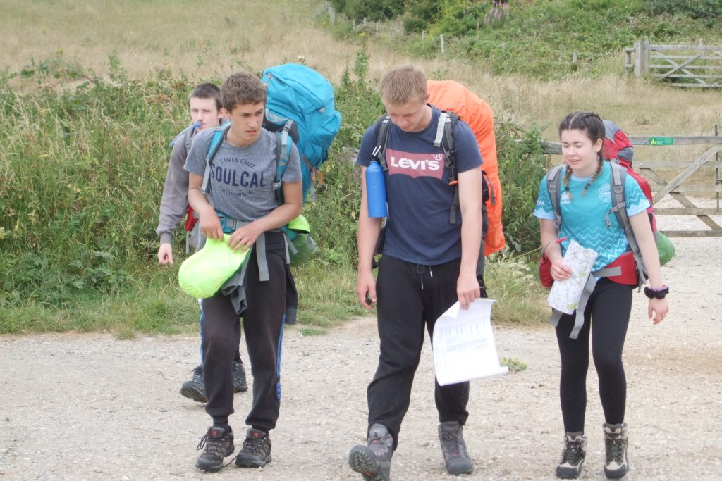Three young men and one young woman on DofE expedition wearing rucksacks and walking
