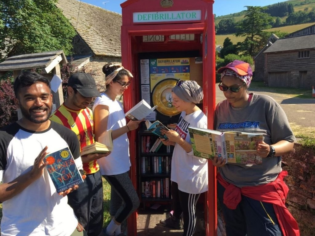 Group of four DofE participants on expedition in front of red telephone box holding maps