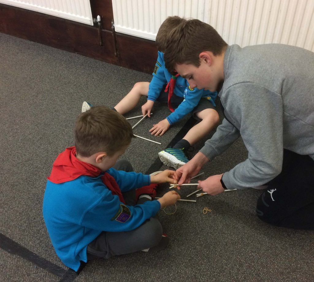Ralph helping two young Scouts