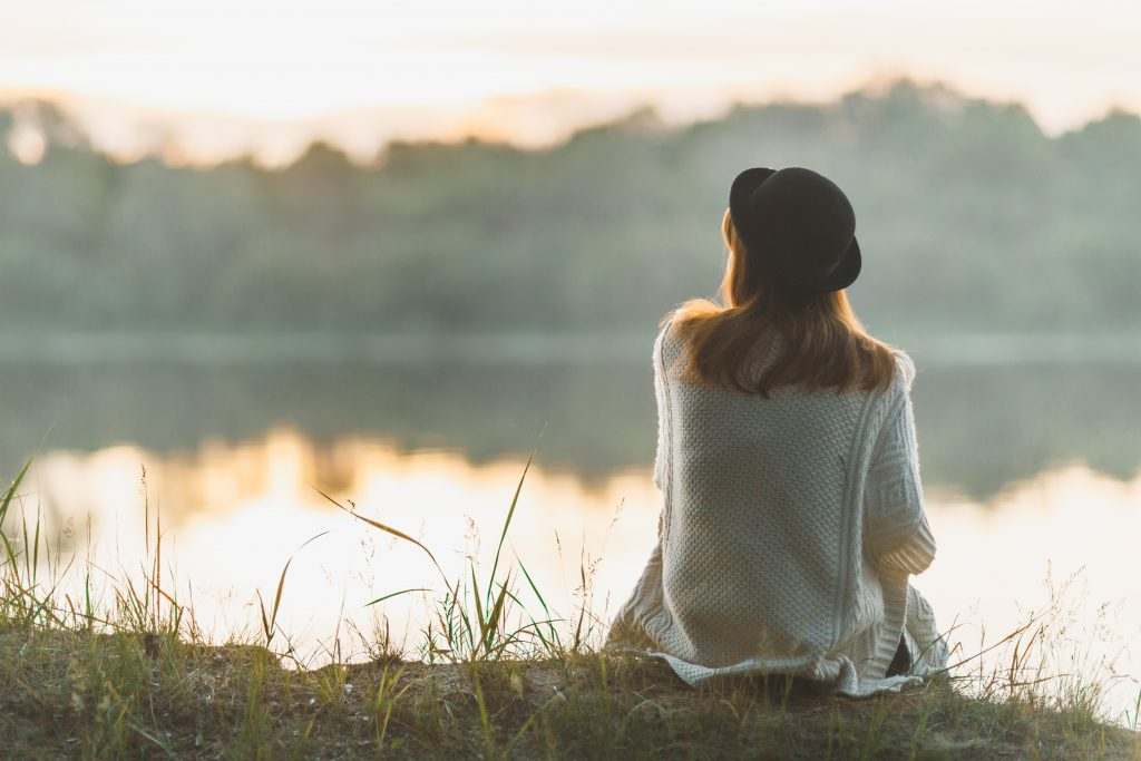 Woman in black hat sitting by a lake