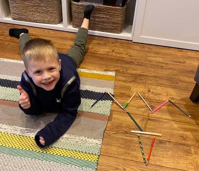 Hayden lying on floor with thumbs up