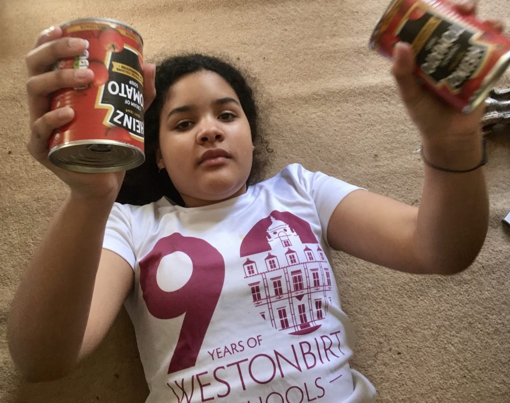 Young girl laying on floor holding two cans