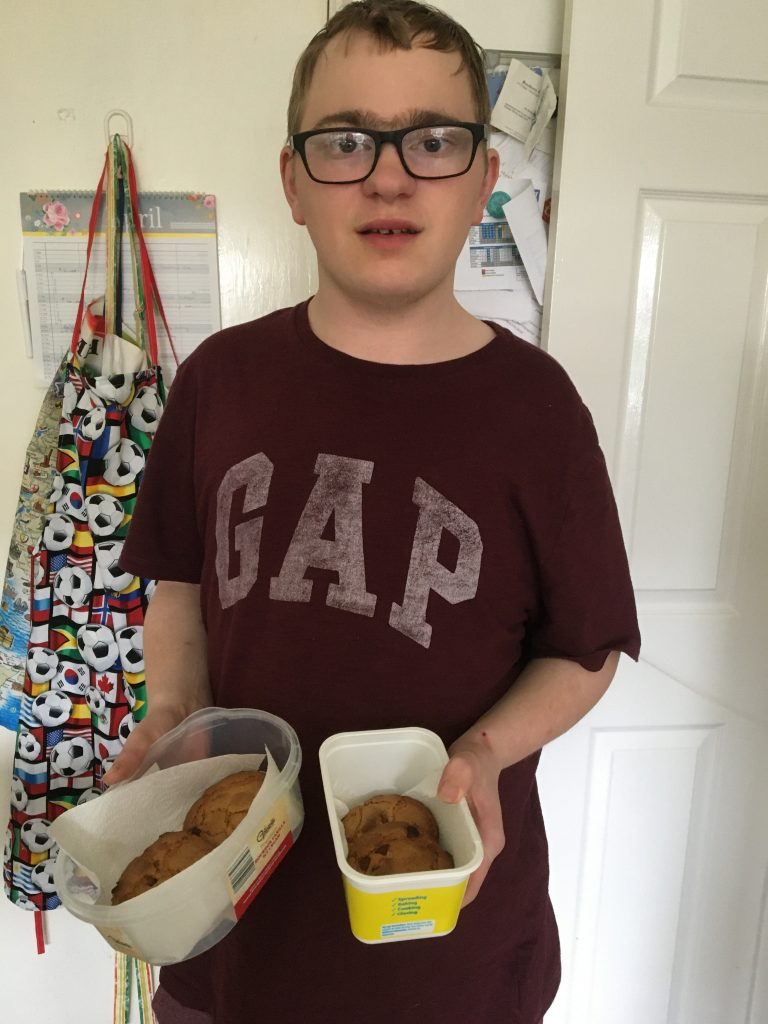 Young man wearing t-shirt holding baked goods