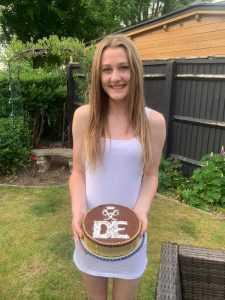 Young woman in white dress holding cake with DofE logo