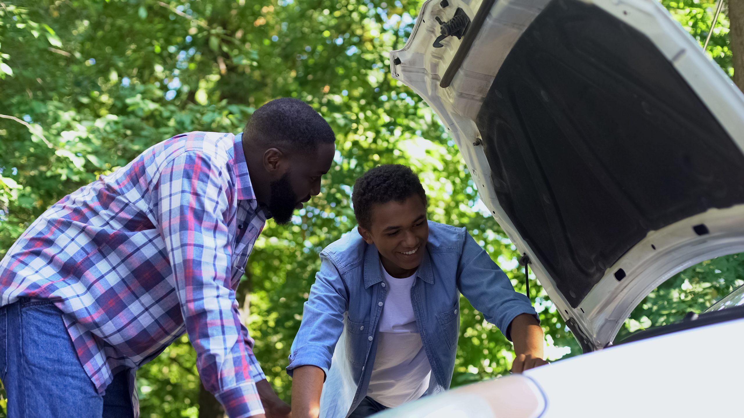 Young man learning car mechanic skills from older male teacher