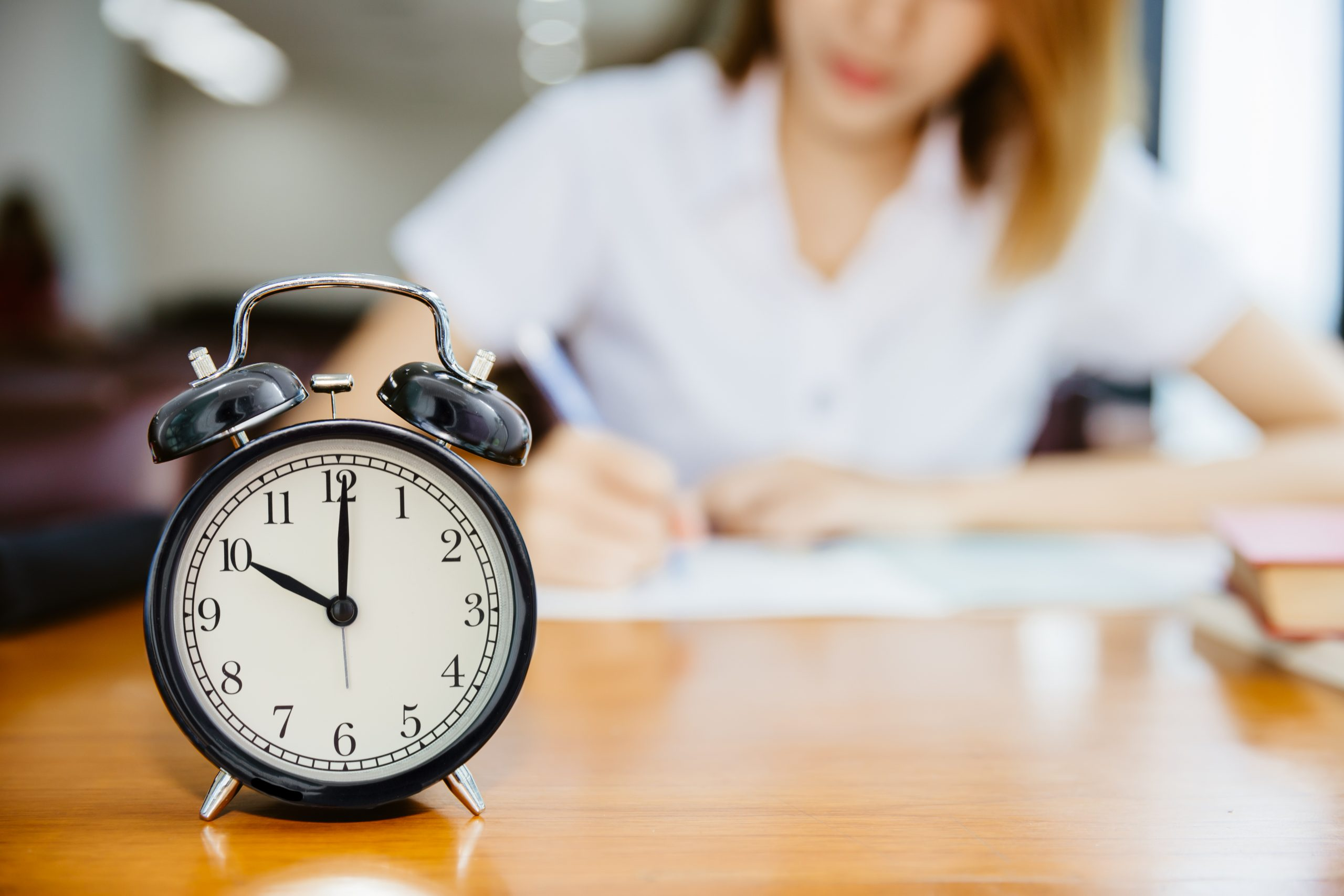 Alarm clock on table in front of girl writing in background