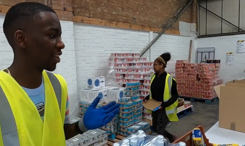 Two young people in high vis jackets working at a food bank