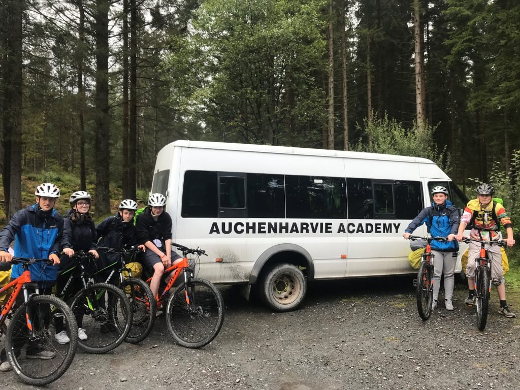 Photo of a white bus with DofE participants on bikes