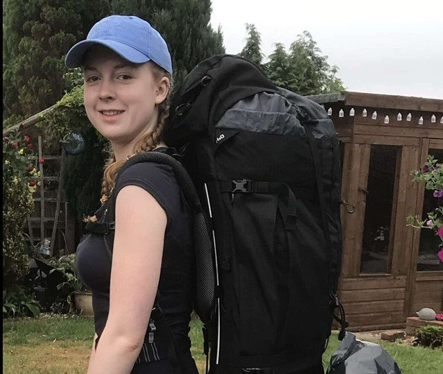 Lydia in black tshirt and blue cap wearing expedition backpack