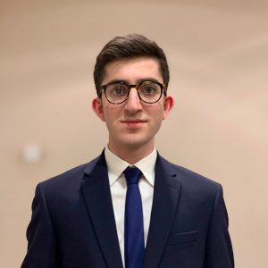 Young man in blue suit and tie wearing glasses