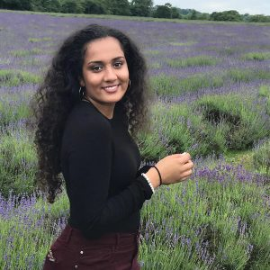 Girl standing in lavender field and smiling