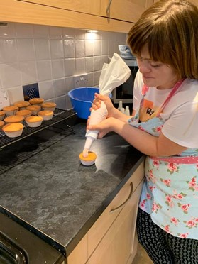 Young woman icing a cupcake in kitchen