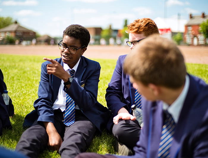 Young people in school uniform sat on grass