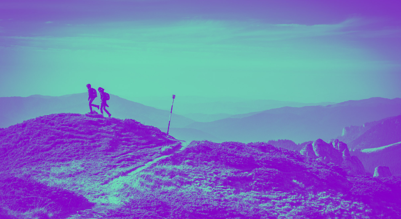 Two people on expedition in the distance on top of mountain wearing backpacks
