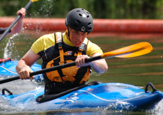 Man kayaking in blue kayak looking determined