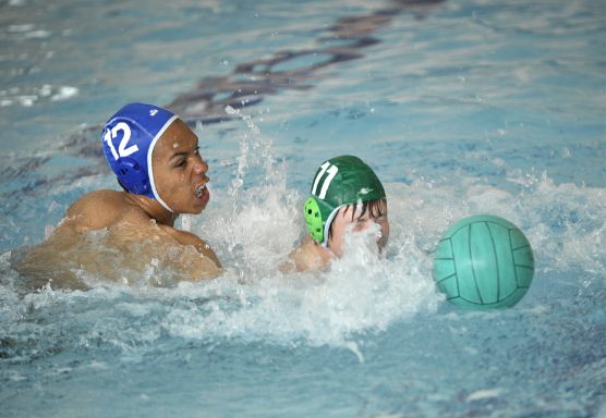Two young people playing with ball in swimming pool