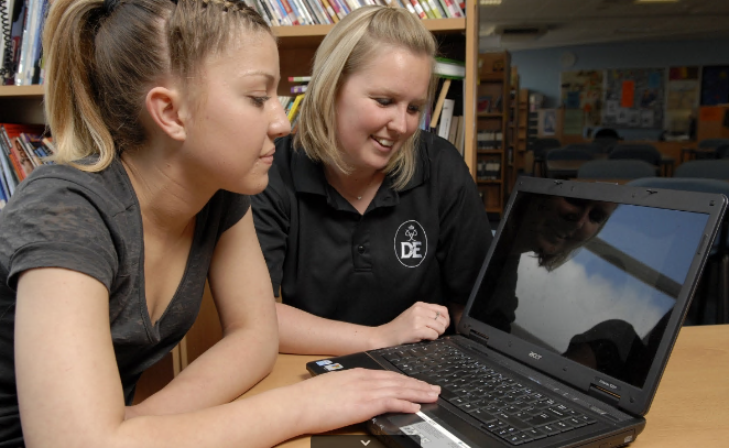 Girl and female DofE leader both looking at a laptop screen smiling