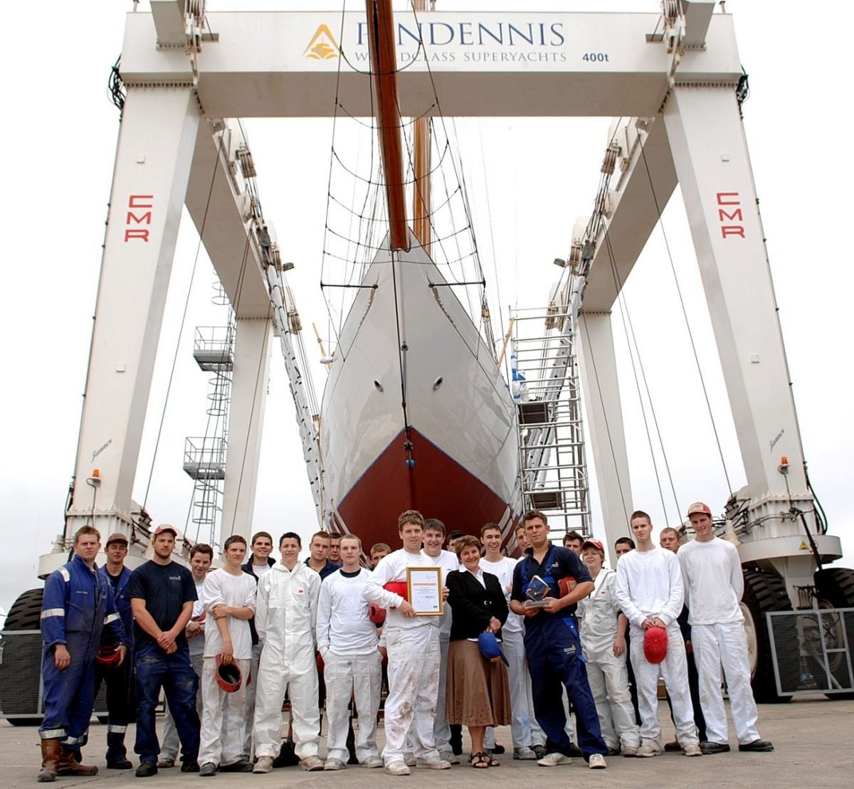 Group of Pendennis Shipyard apprentices stood in front of large yacht
