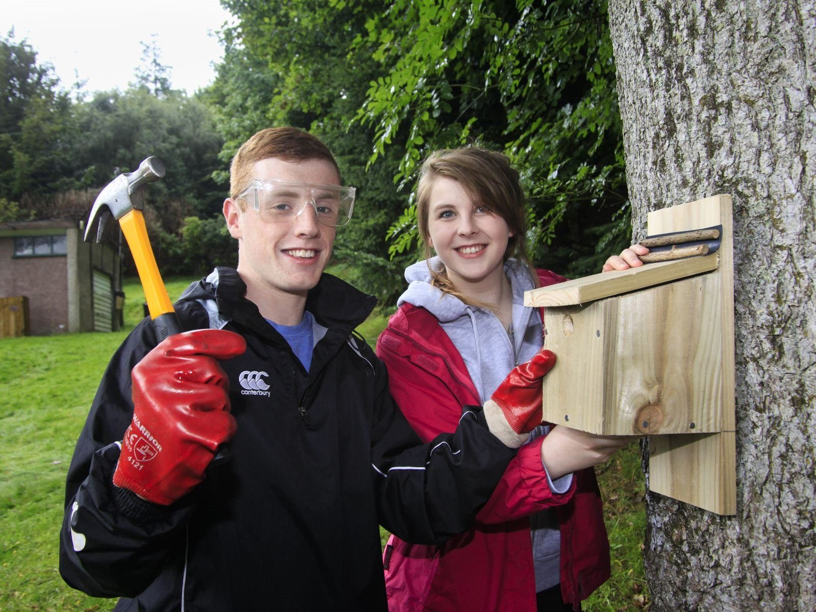 Two young people building a wooden birdbox onto a tree