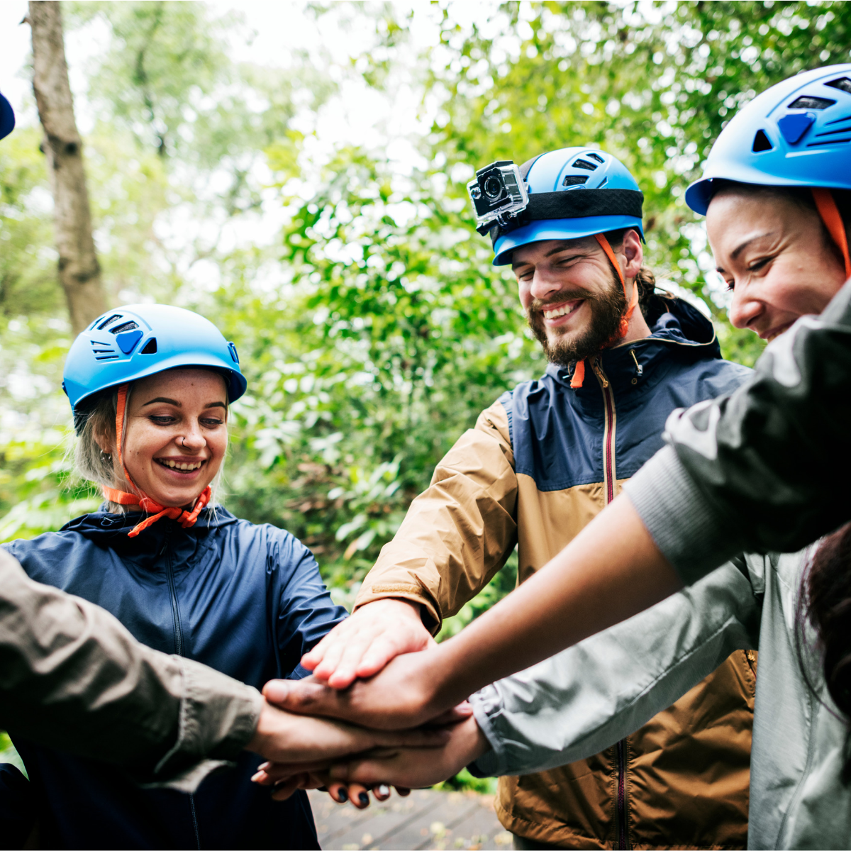 Group of people outdoors happy wearing helmets on expedition, putting hands into a circle