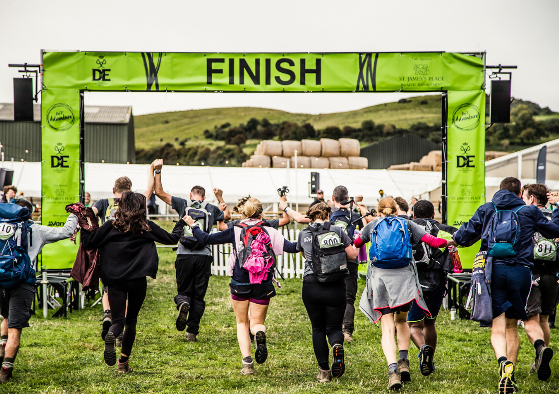 Group with backpacks running towards DofE Adventure finish line