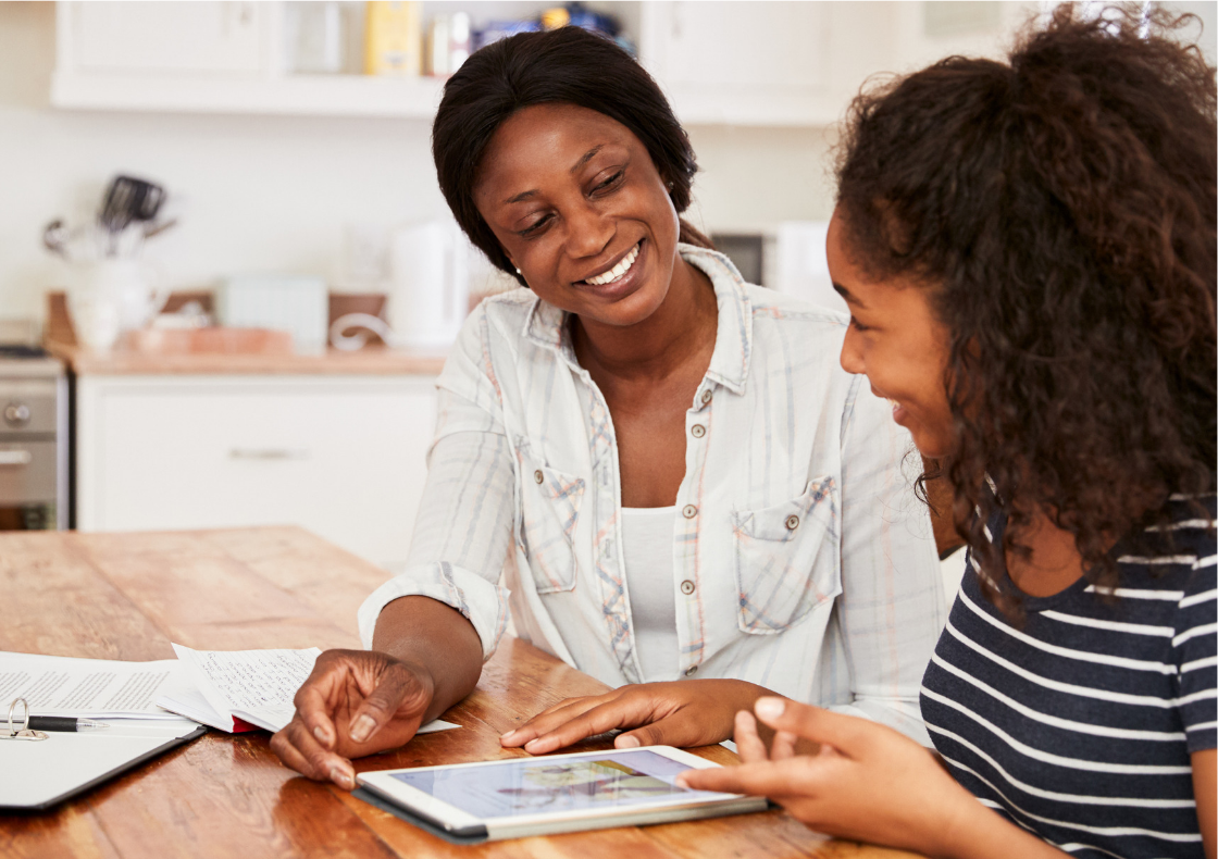 Parent with young person sat at kitchen table both looking at a tablet and smiling
