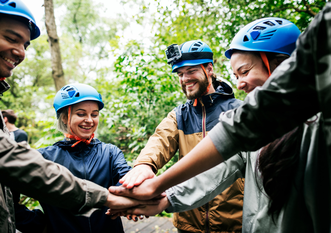 Outdoor group on residential expedition, wearing helmets and putting hands together in a circle