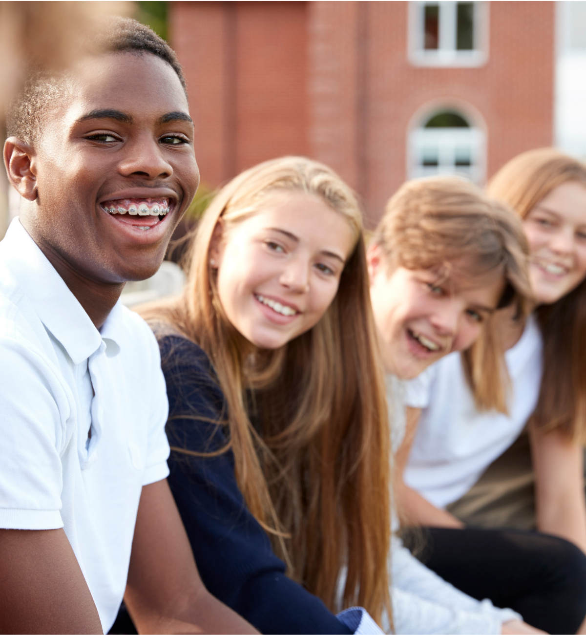 Group of smiling teens in a line