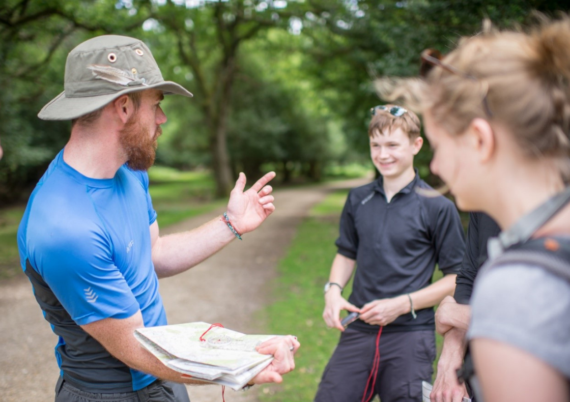 Leader on expedition teaching two young people to read maps