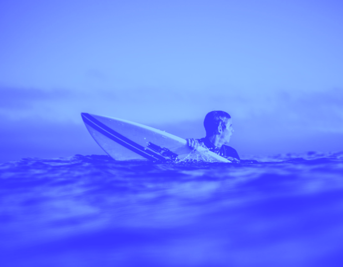 Young man in the sea with a surf board