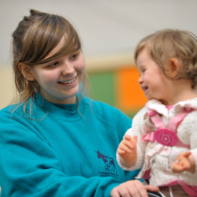 Young woman volunteering with child with additional needs