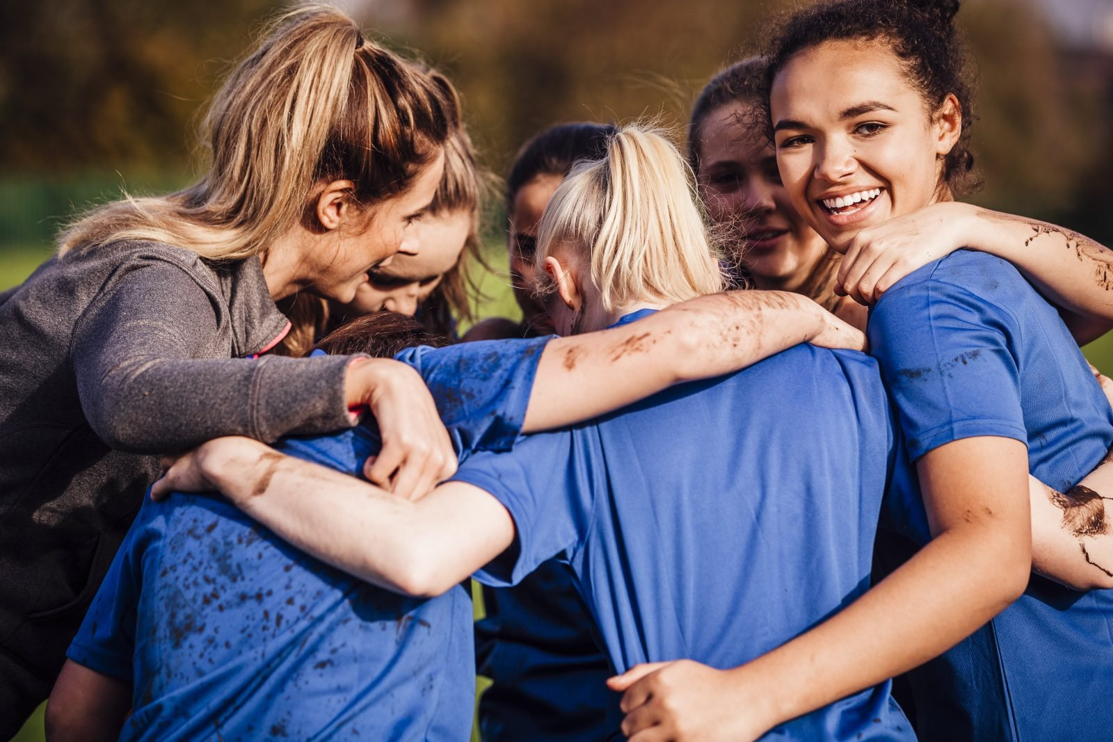 Group of young women and female adult in a football huddle