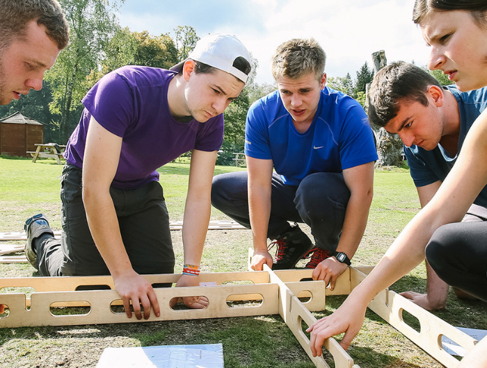 Group of five young people building a wooden object as an icebreaker exercise