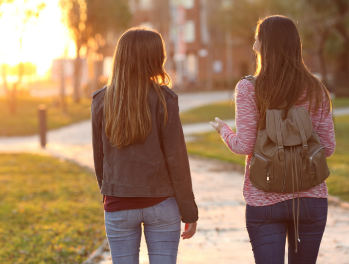 Two teenage girls walking along a path chatting