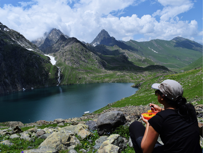 Girl wearing a cap sat eating healthy food at the top of a mountain on her DofE expedition