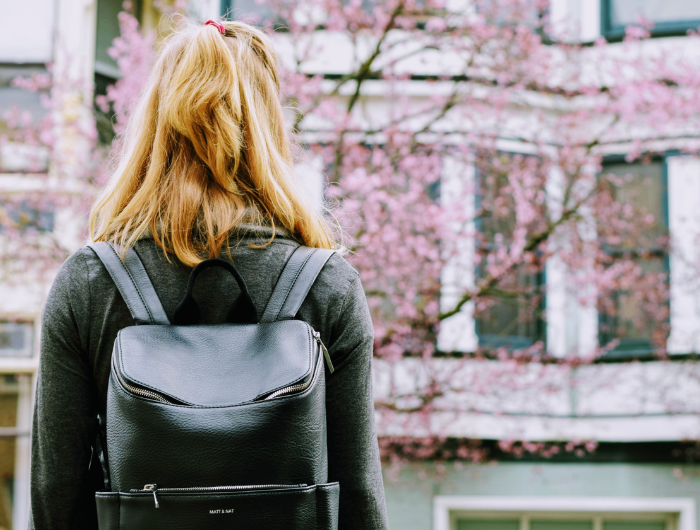 Young blonde woman stood facing a cherry blossom tree wearing a backpack