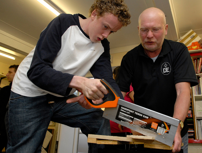 Teenage boy sawing wood while being supervised by a professional