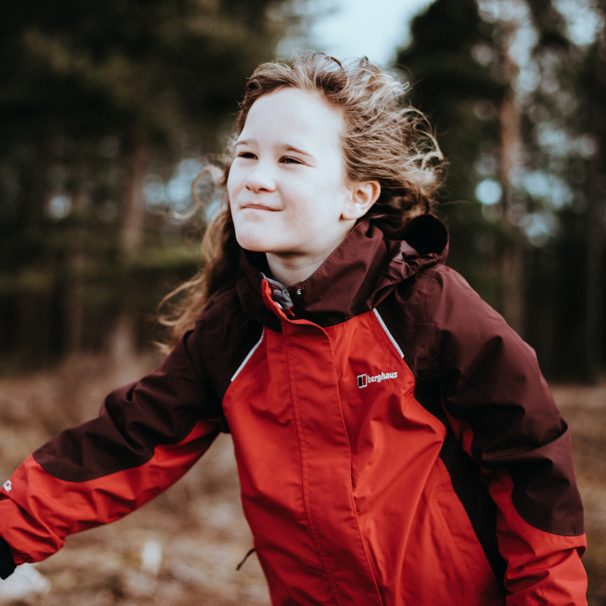 Girl running outdoors in red waterproof coat