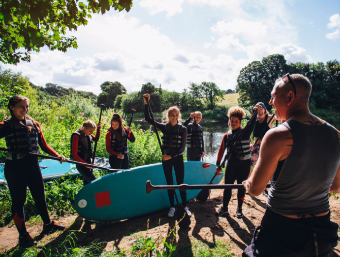 Group of young people and instructor with oars and paddleboards