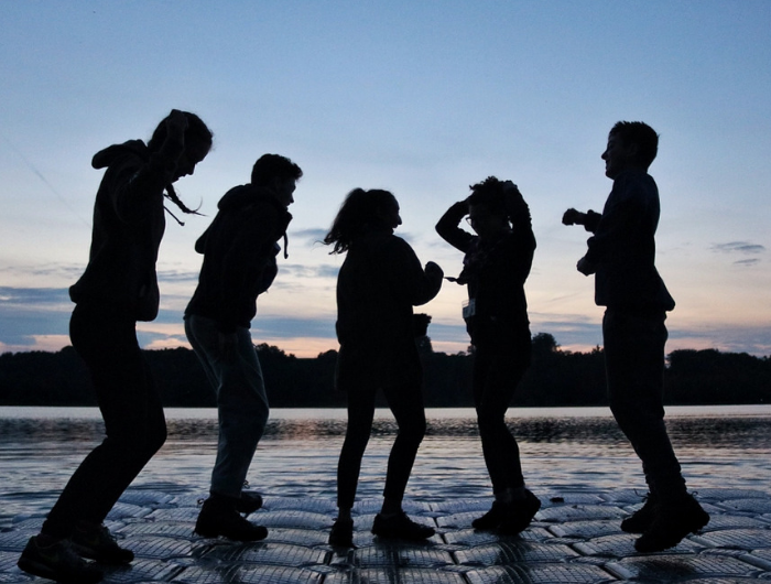 Silhouettes of five young people jumping in front of water