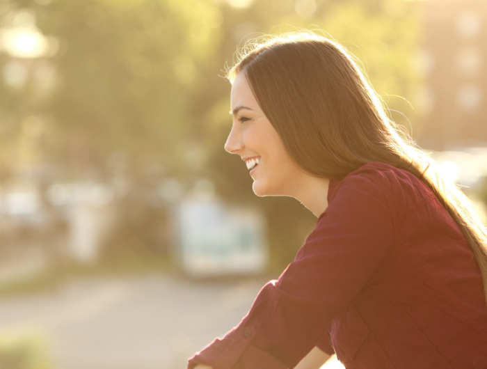 Woman leaning on a surface outside smiling